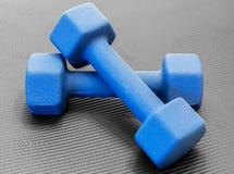 Deux poids bleus de dumbell sur un tapis noir ouvert de yoga d'exercice Photo libre de droits