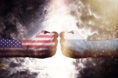 Deux poings se frappant au-dessus du ciel, des Etats-Unis et de la Russie foncés sont en conflit Photographie stock
