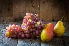 Deux poires et branches jaunes des raisins organiques mûrs sur le CCB en bois Photographie stock libre de droits