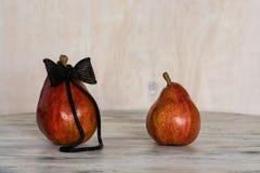 Deux poires rouges sur la table en bois Photo conceptuelle avec les poires Rugueux en bijoux avec un arc Image stock