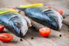 Deux poissons crus de bar avec des tomates-cerises sur un CCB en bois rustique Images stock