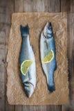 Deux poissons crus de bar avec la tranche de citron sur le fond en bois Photos libres de droits