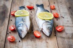 Deux poissons crus de bar avec le citron et les tomates-cerises sur le Ba en bois Photo stock