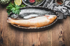 Deux poissons crus de truite dans le plat de cuisson avec des ingrédients sur le fond en bois rustique, vue supérieure Photos libres de droits