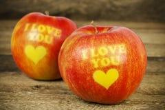 Deux pommes avec une inscription je t'aime sur le bois Image stock