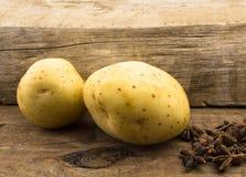 Deux pommes de terre se ferment sur le bois avec l'anis d'étoile Photographie stock libre de droits