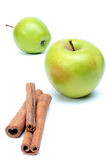 Deux pommes et cannelle juteuses vertes au-dessus de blanc Image stock