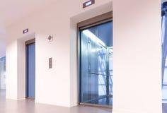 Deux portes des ascenseurs avec les murs transparents dans le bâtiment moderne d'affaires Photos stock