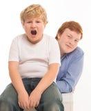 Deux portraits de studio de frères et d'amis de garçons sur jouer blanc de fond Photographie stock