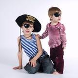 Deux portraits drôles d'enfants de mêmes parents sur le fond blanc Image stock