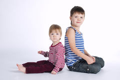 Deux portraits drôles d'enfants de mêmes parents sur le fond blanc Images libres de droits