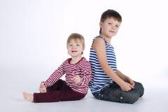 Deux portraits drôles d'enfants de mêmes parents sur le fond blanc Photographie stock