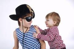 Deux portraits drôles d'enfants de mêmes parents sur le fond blanc Image libre de droits