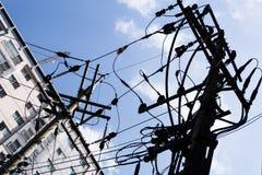 Deux poteaux électriques avec le câblage complexe contre un ciel nuageux bleu image libre de droits