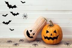 Deux potirons avec les visages peints, les araignées décoratives et les battes dessus Images stock