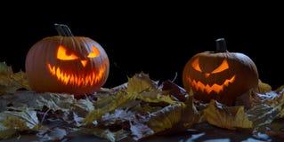 Deux potirons rampants comme lanterne du cric o parmi les feuilles sèches sur le noir Image stock