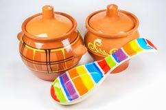 Deux pots d'argile bruns avec la cuillère en céramique colorée sur le fond blanc Photographie stock libre de droits