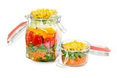 Deux pots en verre avec des agrafes avec les légumes colorés Images stock