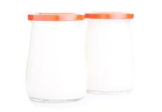 Deux pots en verre de yaourt d'isolement sur le fond blanc Photographie stock libre de droits