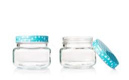 Deux pots en verre vides avec le bleu ont pointillé le couvercle sur le fond blanc Photos stock