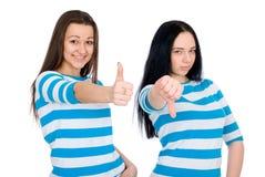 Deux pouces attrayants d'exposition de filles Image stock