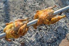 Deux poulets entiers ont rôti et ont grillé sur une broche de broche au-dessus d'un feu, d'une braise et des cendres Photo libre de droits