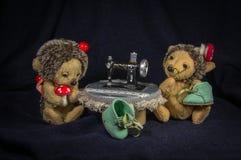 Deux poupées des chaussure-hérissons tout en travaillant à la table avec une machine à coudre Photo stock