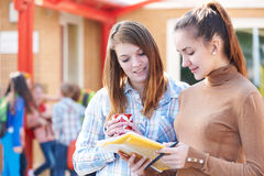 Deux professeurs dans le terrain de jeu avec le s'inscrire au temps de coupure Images stock