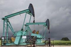 Deux puits de pétrole verts se reposant côte à côte contre les nuages de pluie orageux foncés photographie stock