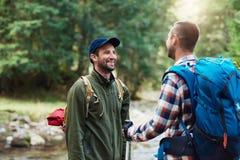 Deux randonneurs de sourire parlant ensemble dans la région sauvage Images stock