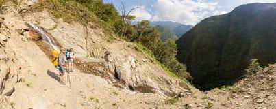 Deux randonneurs de touristes d'hommes croisant la cascade coulent, la Bolivie Image stock