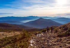 Deux randonneurs marchant sur le fond de montagnes de coucher du soleil de chemin de montagne Image libre de droits