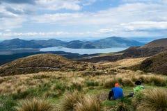 Deux randonneurs regardant la vue du lac Rotoaira et du lac Taupo de la hausse de croisement alpine de Tongariro avec des nuages  images stock