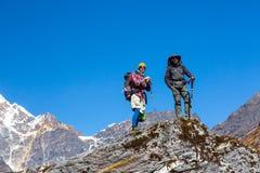 Deux randonneurs restant sur la haute roche en montagnes donnant sur le paysage Photos libres de droits