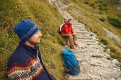 Deux randonneurs se reposant sur une traînée de montagne rocailleuse Photo stock