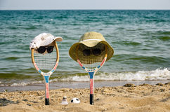 Deux raquettes (boy&girl) se reposent sur la plage Images libres de droits