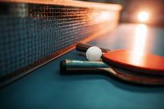 Deux raquettes et boules de tennis contre le filet sur la table Photos libres de droits