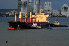 Deux remorqueurs fonctionnants déplaçant un navire porte-conteneurs déchargé Photo stock