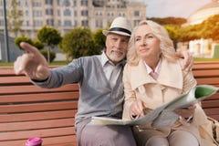 Deux retraités s'asseyent sur le banc et étudient la carte de la ville Photos libres de droits
