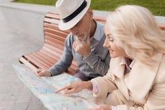 Deux retraités s'asseyent sur le banc et étudient la carte de la ville Photos stock