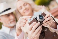 Deux retraités s'asseyent sur le banc et étudient un appareil-photo de vintage Ils vont prendre quelques photos Photos stock