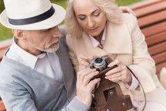 Deux retraités s'asseyent sur le banc et étudient un appareil-photo de vintage Ils vont prendre quelques photos Photo libre de droits