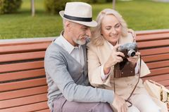 Deux retraités s'asseyent sur le banc et étudient un appareil-photo de vintage Ils vont prendre quelques photos Photographie stock