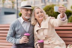 Deux retraités s'asseyent sur un banc avec un verre de café dans leurs mains Ils font des selfies sur un smartphone du ` s de fem Image stock
