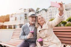 Deux retraités s'asseyent sur un banc avec un verre de café dans leurs mains Ils font des selfies sur un smartphone du ` s de fem Photographie stock