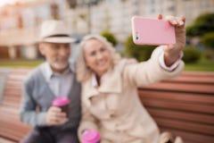 Deux retraités s'asseyent sur un banc avec un verre de café dans leurs mains Ils font des selfies sur un smartphone du ` s de fem Photo stock