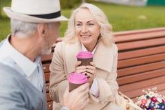 Deux retraités s'asseyent sur un banc avec un verre de café dans leurs mains Ils regardent l'un l'autre avec la tendresse Photo libre de droits