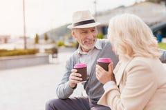 Deux retraités s'asseyent sur un banc avec un verre de café dans leurs mains Ils regardent l'un l'autre avec la tendresse Photos libres de droits