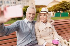 Deux retraités s'asseyent sur un banc avec un verre de café dans leurs mains Ils reposent étreindre et faire des selfies Images stock