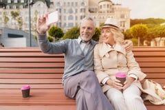 Deux retraités s'asseyent sur un banc avec un verre de café dans leurs mains Ils reposent étreindre et faire des selfies Photo stock